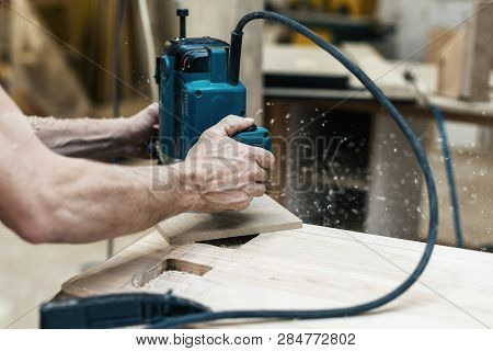 Hobby wood concept. Cropped photo of cabinetmaker craftsman handcraft plunge tool in wood make furniture in work shop or workroom poster
