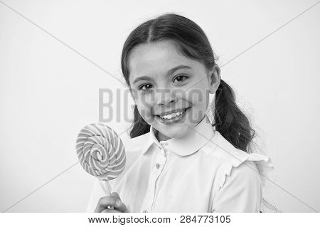 Candy lollipop favorite treats of pupil. Having fun with candy. Girl kid ponytails hairstyle eat sweet lollipop. Girl pupil school uniform like sweet lollipop yellow background. Her favorite flavor. poster