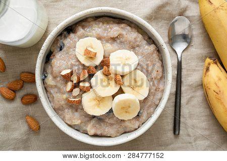 Oatmeal Porridge With Banana And Nuts, Top View. Vegan, Vegetarian Breakfast Meal, Healthy Eating Co