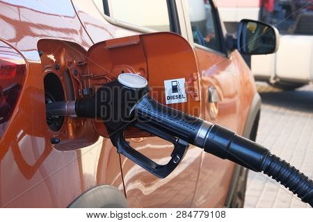 Car Fill With Diesel At Gas Station. Pumping Diesel Fuel In Orange Car At Gas Station Close Up.
