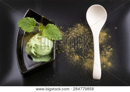 Green Tea Ice Cream In A Bowl With A Teaspoon On A Black Plate. Top View