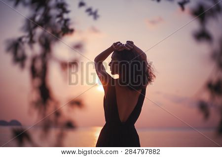 Young Beautiful Sensual Woman In A Stylish Dress With An Open Back Is Standing On The Seashore At Su
