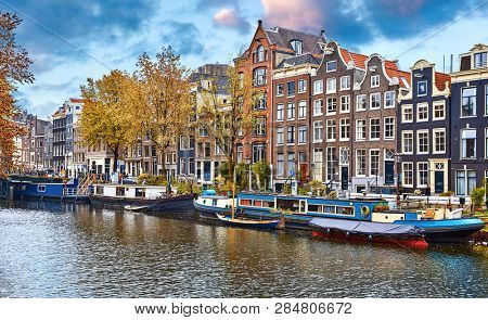 Amsterdam, Netherlands. Floating Houses, houseboats and boats at channels by banks. Traditional dutch dancing houses among trees. Evening autumn street above water blue sky with clouds.