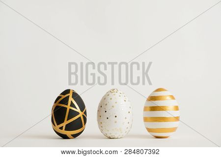 Three Easter Golden Decorated Eggs Isolated On White Background. Minimal Easter Concept. Happy Easte