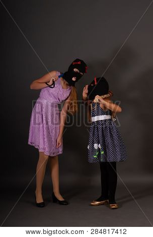 Two Teenage Hooligans In Bright Smart Dresses, But In Gangster Balaclava Hats With Weighty Batons Wh