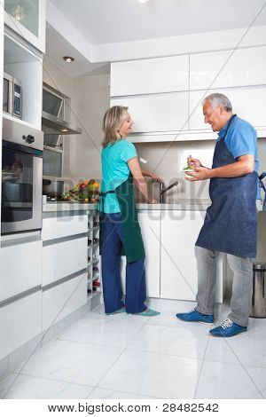 Woman working at kitchen counter while man eating salad