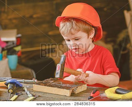Concentrated Kid Working With Hammer. Little Boy Gaining New Skills. Preschooler Learning To Hammer