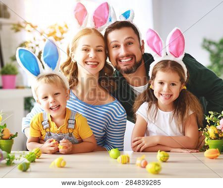 Easter. Happy Family Mother Father And Children Are Preparing For The Holiday Home With Eggs