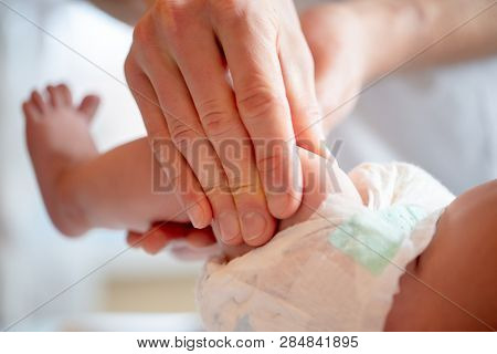 Photo of hands of massage therapist making foot massage to small child/
