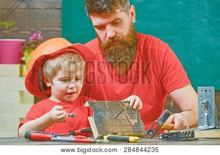 Father, Parent With Beard Teaching Little Son To Use Hobnails And Hammer. Masculine Duties Concept.