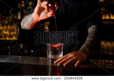 Bartender Adding A Bitter To The Delicious Cocktail From The Special Dasher Bottle On The Bar Counte
