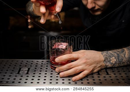 Bartender Adding A Bitter To The Cocktail Glass With Ice Cube From The Special Dasher Bottle On The