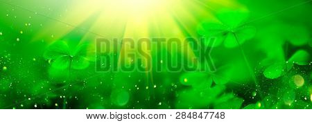 St. Patrick's Day green background decorated with shamrock leaves. Patrick Day pub party celebrating. Abstract Border art design Magic nature backdrop. Widescreen clover art design with copy space