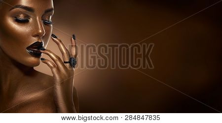 Beauty Black girl fashion art portrait over dark brown background. Professional make-up and manicure. Sexy Afro American young woman with beautiful skin. Accessories, ring. Black nails and lipstick