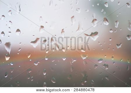 The Colorful Lights Of A Rainbow Behind A Rainy Windowpane With Raindrops.