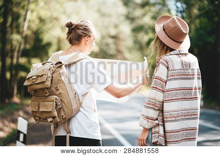 Man And Woman Traveling Together And Hold In Hands Location Map And Searching Directional Among Tree