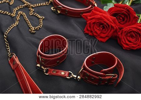 Erotic Games. Top View Of Bdsm Leather Stuff: Red Handcuffs And Roses Against Of Black Silk Fabric