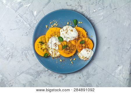Delicious Healthy Fruit Breakfast. Sliced Persimmon With Yogurt, Brown Sugar, Pine Nuts And Fresh Mi