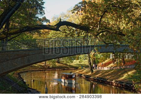 RIGA, LATVIA - OCTOBER 15, 2016: People on the tour boat in city canal. Boat tour by canal and Daugava river is one of Must Do for tourists in Riga