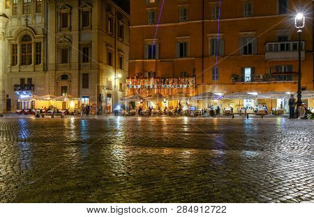 Rome, Italy - September 30 2018: Late Night On The Piazza Navona As Beams Of Purple Rocket Flares Li