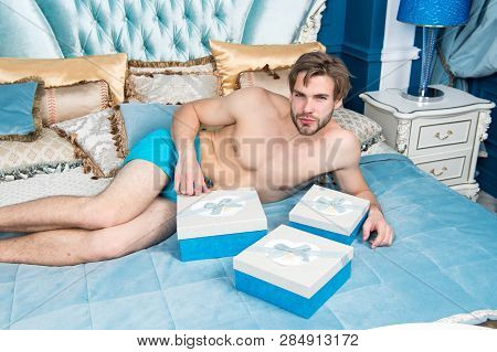 Man handsome lover and gift. Surprise for sweetheart. Gifts for darling. Birthday morning. Romantic surprise. Valentines day celebration. Sexy surprise for female. Man in luxury bedroom with gift box. poster