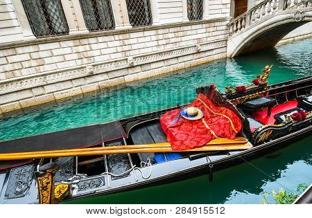 A Fish Swims Under A Venetian Gondola Filled With Oars, Gondolier Hat, Striped Shirt And Red Blanket