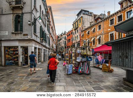Venice, Italy - September 18 2018: Tourists Shop For Souvenirs And Purses In Front Of A Market As Th