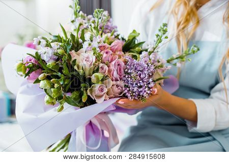 Cropped View Of Female Florist Holding Bouquet With Lilac And Roses In Flower Shop