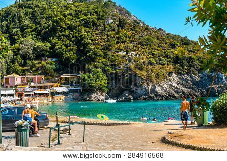 Corfu, Greece - September 16 2018: A Young Couple On A Motorcycle Arrive At A Small Bay Near Palaiok
