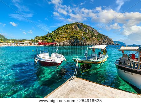 Corfu, Greece - September 18 2018: Boats Docked In The Crystal Turquoise Waters Near The Shore Of Th