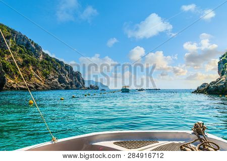 A Small Boat Heads Towards Other Boats And Out Of The Palaiokastritsa  Bay Towards The Aegean Sea On