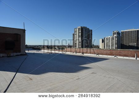 Flat Open Roof On The Top Of An Apartment Building Under A Clear Blue Sky