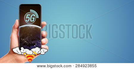 male hand hold launching 5G smartphone with planet Earth on screen, isolated on blue background. Elements of this image furnished by NASA
