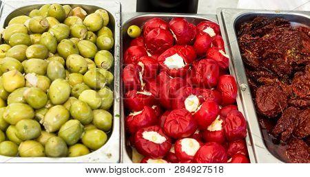 Assortment variety of handmade artisan marinated brine cured antipasti tapas green olives with herbs sun dried and stuffed tomatoes at mediterranean farmers market. Italian Spanish Greek cuisine poster