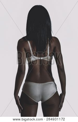 Rear view of mixed race black woman in underwear on white background.