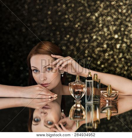 Beautiful woman and collection of perfumes bottles on sparkling background. Space for text.