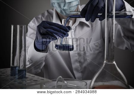 Professional Scientist Holding A Test Tube And Tablet While Making A Research