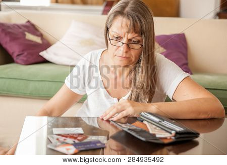 Mature woman is upset, looking at the credit cards taken out of wallet
