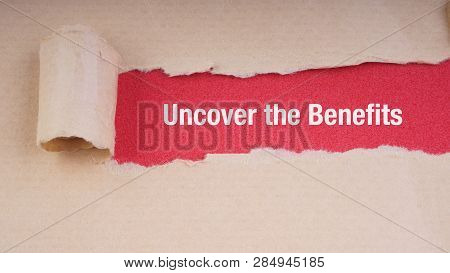 Uncover The Benefits Text On Brown Envelope And Torn Paper. Concept Image