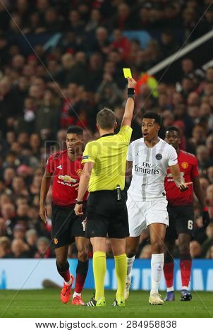MANCHESTER, ENGLAND - FEBRUARY 12 2019: Referee Daniele Orsato shows a yellow card to Presnel Kimpembe of PSG during the Champions League match between Manchester United and Paris Saint-Germain