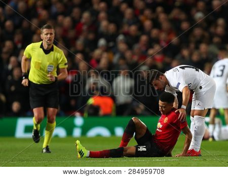 MANCHESTER, ENGLAND - FEBRUARY 12 2019: Jesse Lingard of Manchester United gets helped to his feet by Juan Bernat of PSG during the Champions League match between Manchester United and PSG