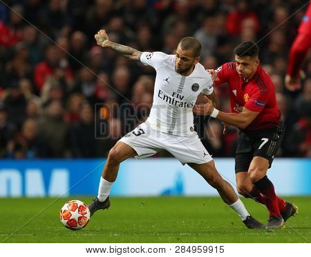 MANCHESTER, ENGLAND - FEBRUARY 12 2019: Dani Alves of PSG  and Alexis Sanchez of Manchester United during the Champions League match between Manchester United and Paris Saint-Germain at Old Trafford