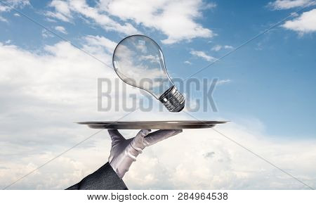 Cropped Image Of Waitresss Hand In White Glove Presenting Lightbulb On Metal Tray As Symbol Of New I