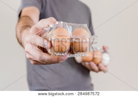 Caucasian Man With Gray Tshirt Showing A Plastic Egg Box Full Of Hen Eggs