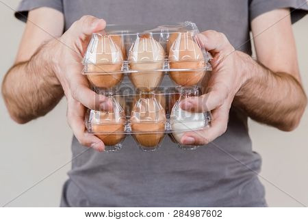 Caucasian Man With Gray Tshirt Holding Two Plastic Egg Boxes Full Of Hen Eggs.