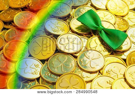 St Patrick's Day background. Golden coins with shamrock, green bow tie and rainbow, St Patrick's day symbols. St Patricks day festive card