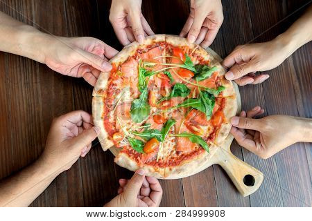 People Hands Taking Slices Of Salmon Pizza With Rocket And Tomato. High Angle Friend Group Hands Gra