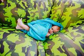 From above little child in blue towel lying on khaki pouf poster