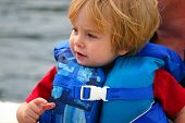 Close-up of a young boy in a lifejacket on a boat poster