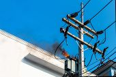 power pylon overload or electric short circuit at transformer on poles and fire or flame with smoke on blue sky poster